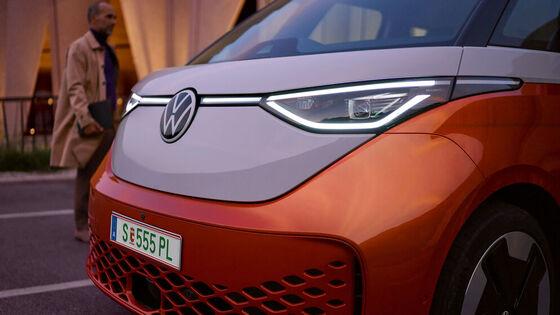 Ein roter Multivan 6.1 fährt auf einer Straße über Schutzweg. Eine Frau mit gelben Oberteil quert den Schutzweg.