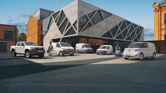Vier VW Nutzfahrzeug-Modelle stehen auf einer Baustelle