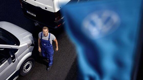 Ein Frau scrollt auf ihrem Handy, das auf dem Dach eines VW liegt