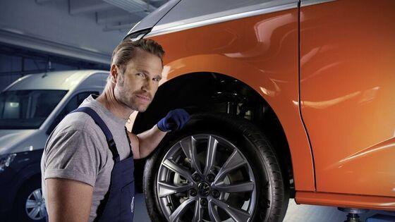 Ein Mann geht mit einem Paket unter dem Arm von einem VW Nutzfahrzeug Modell weg